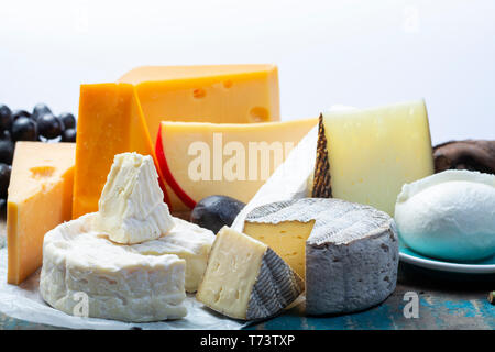 Famous European cheeses in assortment, Dutch red ball Edam and old cheeses with holes, Spanish Manchego cheese, French soft Brie and Camembert, Englis - Stock Image