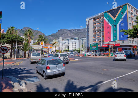 Street in centre of Cape Town, with cars passing, Table Mountain in background, and apartment building in color of Flag. Cape Town, South Africa, - Stock Image