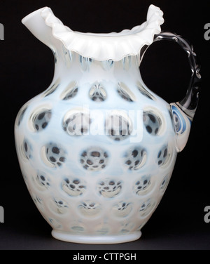 Side view of a Fenton coin dot French opalescent glass pitcher. - Stock Image
