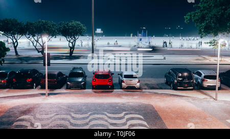Long exposure of Avenida Atlantica and busy Copacabana Beach at night with Cariocas and tourists practicing sporting activities. - Stock Image