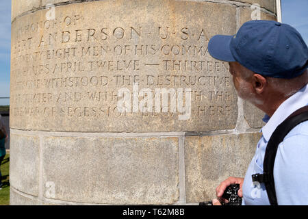 Man reading an inscription at Fort Sumter near Charleston in South Carolina, USA. The inscription is in memory of the defence of the fort as the openi - Stock Image
