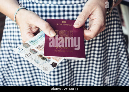 Close up of woman with passport and banknotes. - Stock Image