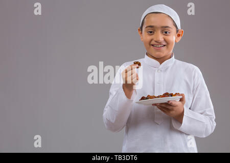 Young Muslim boy wearing cap smiling and eating dates - Stock Image