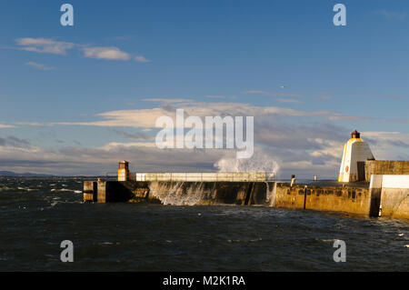Waves breaking over the harbour wall at high tide, at the entrance to Burghead Harbour, Morayshire, Scotland. March. - Stock Image