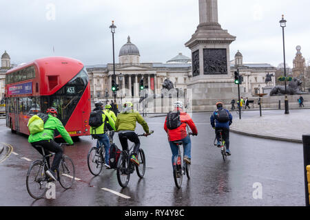 Cycling in the city: A group of cyclists enter the roundabout on Trafalgar square behind a bus on a wet and cloudy winter day in London - Stock Image