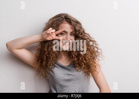Young beautiful cheerful woman in studio, fingers forming V for victory. - Stock Image