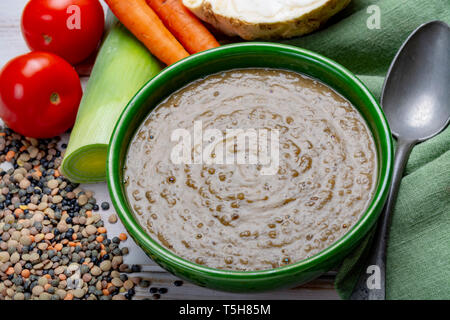 Tasty vegetarian food, green bowl with lentils soup with vegetables, good for vegans, close up - Stock Image