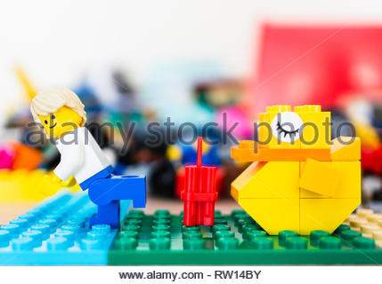 Poznan, Poland - February 15, 2019: Man running away from dynamite laying in front of a sleeping yellow duck. - Stock Image