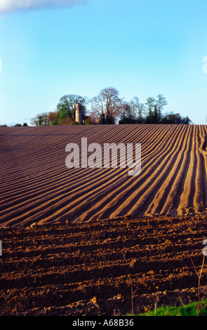 Ploughed field and church near Norwich England - Stock Image