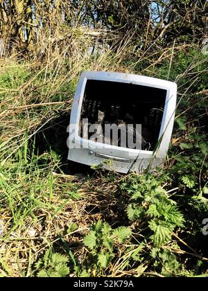An old and out of date computer monitor that has been dumped in wasteland in a fly tipping or waste concept image - Stock Image
