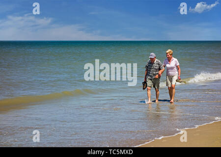 Happy elderly couple paddling in shallow sea water on sandy beach along the coast in summer - Stock Image