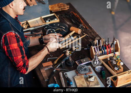 close up side view photo. craftsman choosing the instrumnet for working. copy space - Stock Image