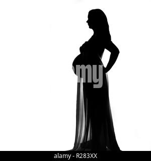 Sillhouette profile of a nude pregnant woman draped in chiffon. - Stock Image