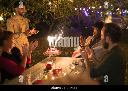 Happy friends celebrating birthday with sparkler cake at garden party table - Stock Image