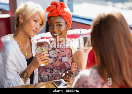 Young women friends drinking cocktails, posing for photograph in restaurant - Stock Image