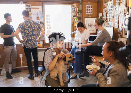 Creative business people with dog working and eating in office - Stock Image