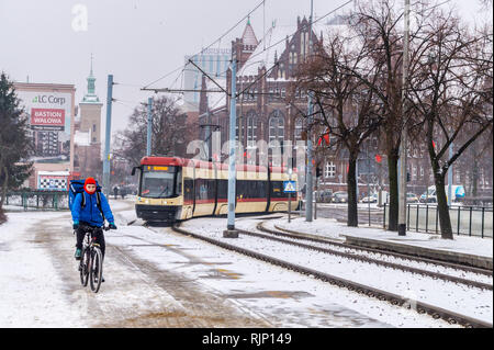 A mano on a bicycle with a tram approaching in snow, Plac Solidarnisci, Gdańsk, Poland - Stock Image