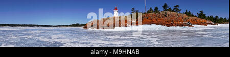 Panoramic view of East Lighthouse, buildt in 1850s, and thick ice cover on Eastern Georgian Bay in Killarney, Ontario, Canada - Stock Image
