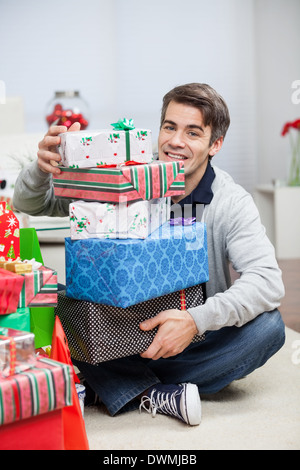 Man With Stack Of Christmas Presents At Home - Stock Image