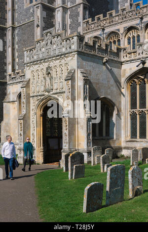 Church porch Suffolk, view of a tourist couple emerging from the late medieval (1525) great porch of the Church of St Peter & St Paul in Lavenham, UK. - Stock Image