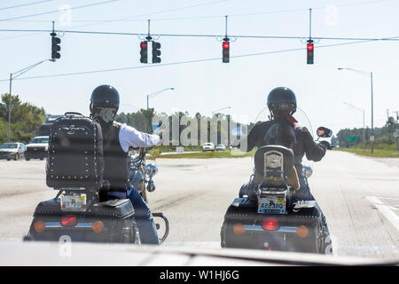 Florida West Frostproof US Route 27 red light traffic intersection stop custom bike motorcycle cruiser touring man woman couple - Stock Image