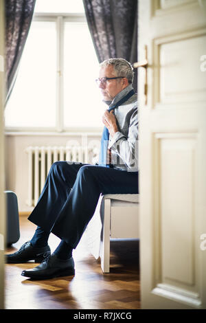 Mature businessman with glasses on a business trip in a hotel room, getting dressed. - Stock Image