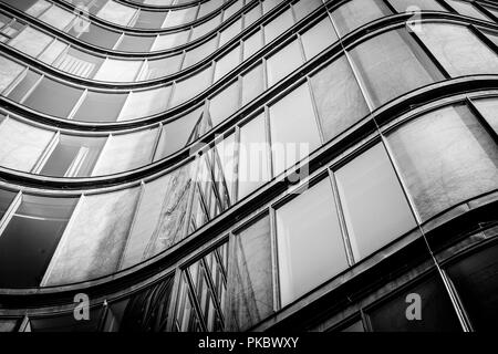 Curved building with shiny windows with reflections in black and white tone - Stock Image
