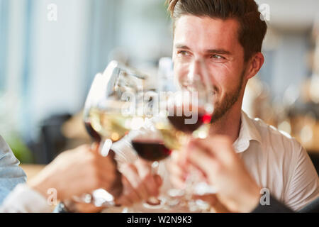 Man toasting with a glass of wine at a celebration in the restaurant - Stock Image