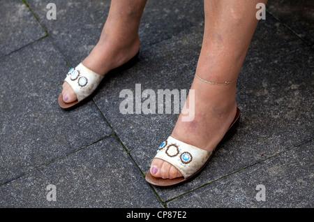 Frauenfüße mit Nylonstrümpfen und mit Schmucksteinen besetzten Sandaletten, Woman´s legs and - Stock Image