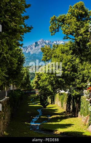 Summer river channel and mountains at Levico Terme, Trentino, Italy - Stock Image