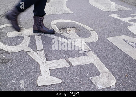 pedestrian crossing accross curved bicycle asphalt line, one person, conflict of interests - Stock Image