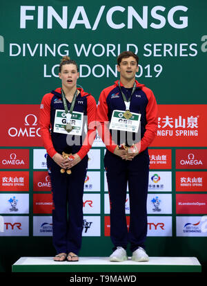 Great Britain's Thomas Daley and Grace Reid on the podium after they win a gold medal 3m Mixed Synchro Springboard during day three of the Diving World Series at London Aquatics Centre, London. - Stock Image