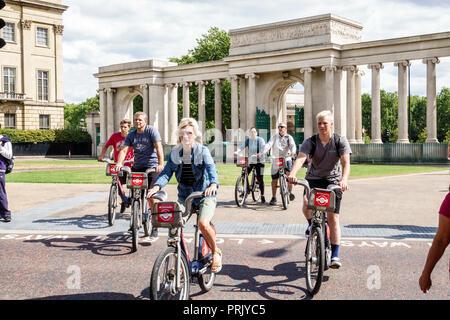 London England United Kingdom Great Britain Hyde Park Corner Decimus Burton's Ionic Screen gate columns man woman boy teen family cyclist bicycle Sant - Stock Image