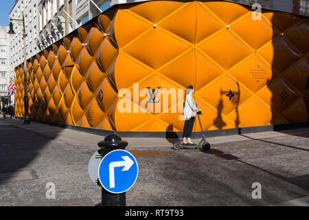 A lady on an electric scooter passes the temporary renovation hoarding of luxury brand Louis Vuitton in New Bond Street, on 25th February 2019, in London, England. - Stock Image