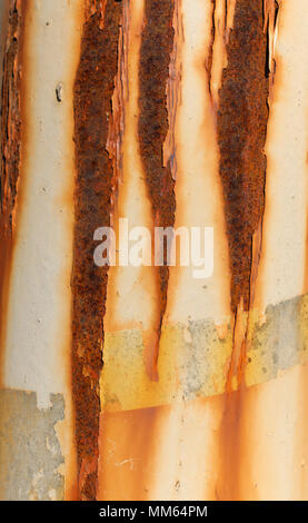 A closeup photo of an exterior of a metal pipe with some vertical lines and cracked old paint. - Stock Image