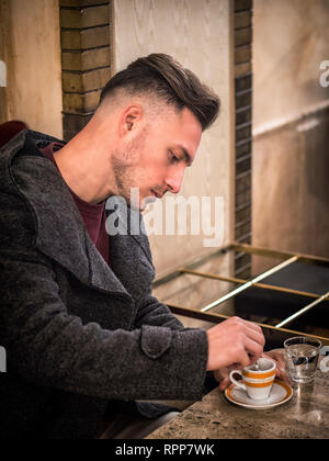 Attractive Young Man Drinking Espresso Coffee at Bar - Stock Image