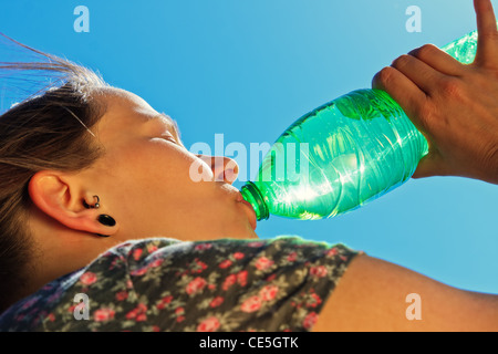 Thirsty woman is drinking fresh water on a sunny day - Stock Image