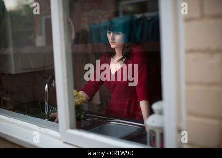 Disappointed woman standing in kitchen - Stock Image