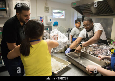 Volunteers at a community kitchen prepare a meal for diners in need. - Stock Image