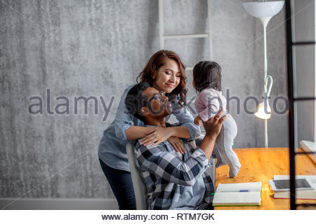 positive parents playing with the baby girl in the modern room, close up side view photo.happy parenthood - Stock Image