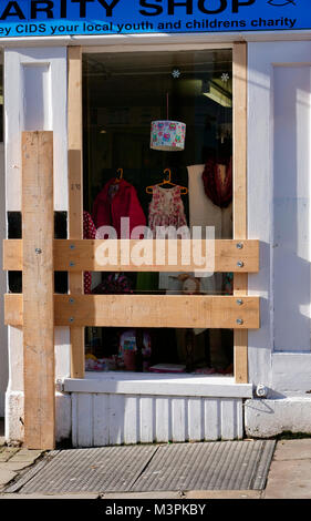 All boarded up. Ashbourne town centre shop windows are boarded up for the start for the Ashbourne Royal Shrovetide - Stock Image