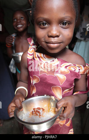 Togolese small girl holding her bowl of rice. Lome. Togo. - Stock Image