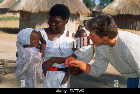 African woman holding two babies in her arms in front of village hut in rural Zimbabwe  visiting with female tourist - Stock Image