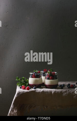Homemade classic dessert Panna cotta with raspberry and blueberry berries and jelly in jars, decorated by mint leaves over linen table cloth with grey - Stock Image