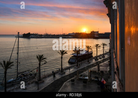 The sun sets over the harbor port as boats dock along the waterfront promenade in the coastal city of Brindisi, Italy, in the Puglia region - Stock Image