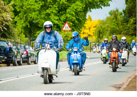 A group of modern vintage aged mods cycling along the Cheshire countryside in a gang out cycling in sunshine,  Near - Stock Image