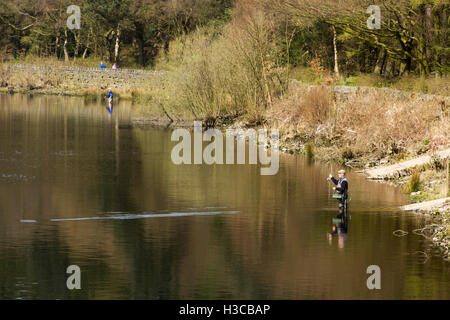 Man fly--fishing at Turton and Entwistle reservoir, Lancashire. The reservoir supplies drinking water to Bolton. - Stock Image