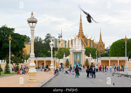 Pedestrians enjoying the early evening in front of the main gates to the Royal Palace complex in Phnom Penh, Cambodia. The gilt spires of the Throne H - Stock Image