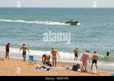 West Bay, Dorset, UK.  27th June 2019. UK Weather.  Sunbathers on the beach at the seaside resort of West Bay in Dorset enjoying a day of clear blue skies and scorching hot sunshine.   Picture Credit: Graham Hunt/Alamy Live News - Stock Image