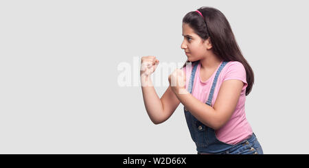 Profile side view portrait of serious or angry young girl in pink t-shirt and blue overalls standing with fists boxing hands and ready to attack. indo - Stock Image